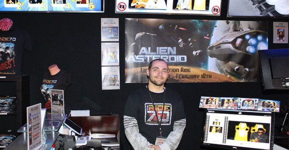 Ride Crew Supervisor Cesar stands with some of the high scores behind him. Alien Asteroid will be available until Feb 18.